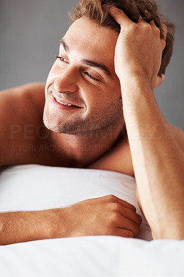 Buy stock photo Shot of a shirtless young man lying on a bed at home