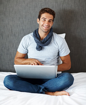 Buy stock photo Portrait of a happy young man using laptop while sitting on his bed at home