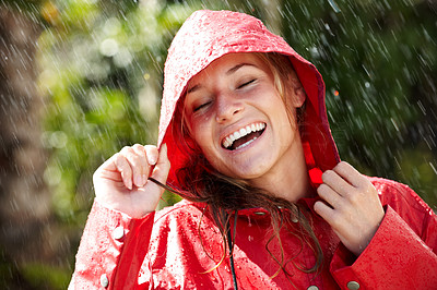 Buy stock photo Pretty young female holding a red raincoat hat on head and enjoying the rain - Outdoors