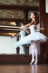 Young ballerina dancing gracefully next to mirror