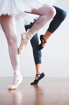 Buy stock photo Low angle view of two ballet dancer's legs in tights, ballet shoes and tutus practicing ballet poses