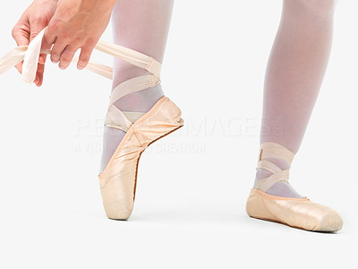 Buy stock photo Low angle view of a ballerina putting on pointes against white background