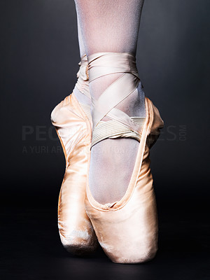 Buy stock photo Low angle shot of a ballerina standing on pointes against black background