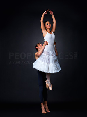 Buy stock photo Full length of two ballet dancers performing against black background - copyspace