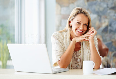 Buy stock photo Portrait of a cheerful middle aged woman with laptop and a tea cup