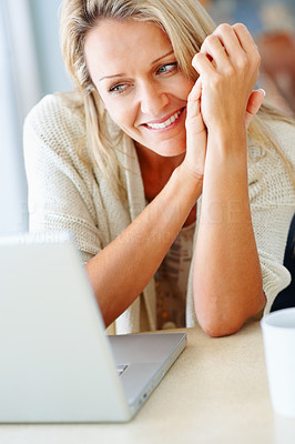 Buy stock photo Closeup portrait of a pretty middle aged woman looking at laptop