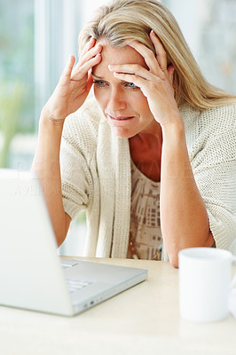 Buy stock photo Portrait of a mature woman with tensed expression looking at laptop screen