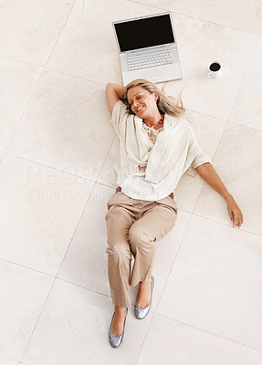 Buy stock photo Top view of a smiling middle aged woman lying on floor by laptop and tea cup