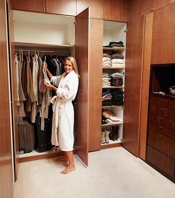 Buy stock photo Portrait of a mature woman selecting clothes near wardrobe after a bath