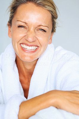 Buy stock photo Closeup portrait of a cheerful mature woman smiling against blue background