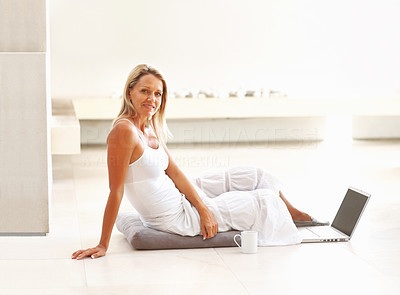 Buy stock photo Side view of a relaxed mature woman sitting on floor and using laptop