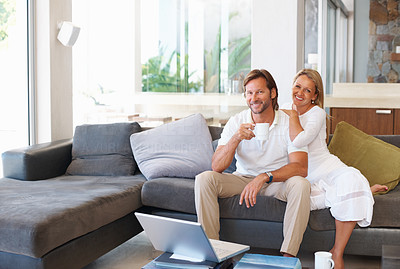 Buy stock photo Portrait of a happy relaxed mature couple sitting together on couch at home