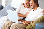 Cheerful mature couple looking at laptop screen on couch at home