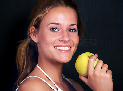Buy stock photo Portrait of happy young girl holding a green apple against black background