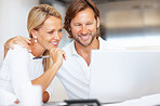 Cheerful mature couple looking at laptop screen together at home