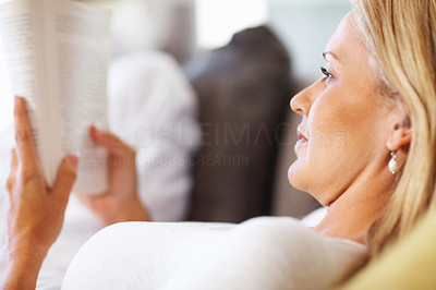 Buy stock photo Closeup of a relaxed mid adult woman reading a book
