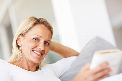 Buy stock photo Closeup of a happy relaxed mid adult woman reading a book