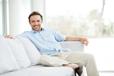 Buy stock photo Portrait of an attractive young man sitting comfortably on couch and smiling - Indoor