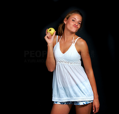 Buy stock photo Portrait of beautiful teenage girl holding an apple and giving a pose against black background
