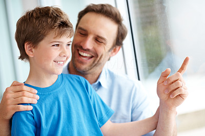 Buy stock photo Happy father pointing at something interesting outside window to his small son
