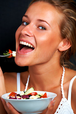 Buy stock photo Portrait of happy young woman eating vegetable salad against black background