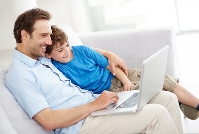 Buy stock photo Portrait of father and son sitting together on sofa using laptop at home