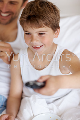 Buy stock photo Portrait of a happy young boy holding remote control  with his father on bed