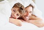 Happy small boy lying on bed with his father under bedsheet
