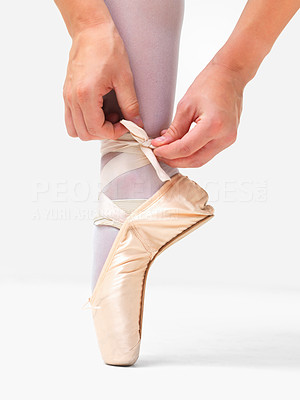 Buy stock photo Closeup of a ballerina putting her shoes on against white background