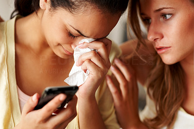 Buy stock photo Closeup portrait of a young girl holding a mobile phone in sorrow with a friend consoling her
