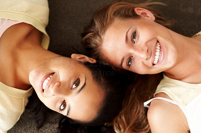 Buy stock photo Closeup portrait of happy young girls lying on ground with their heads together