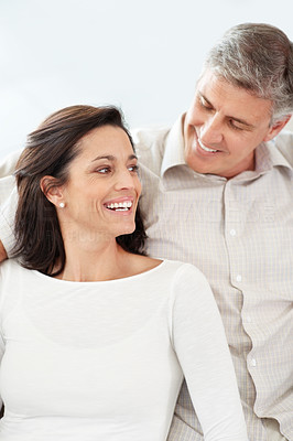 Buy stock photo Portrait of a lovely middle aged couple sitting together and smiling