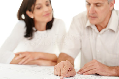 Buy stock photo Portrait of a middle aged man showing some plan to his wife against white