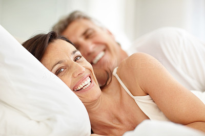 Buy stock photo Portrait of happy mature couple lying in bed and smiling