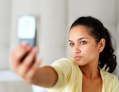 Buy stock photo Portrait of a cute young woman taking picture of herself by her mobile phone