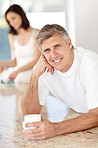 Handsome mature man drinking coffee with his wife standing behind