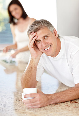 Buy stock photo Portrait of happy mature man holding a coffee mug with his wife standing in background