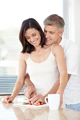 Buy stock photo Portrait of  happy mature couple cutting fruit together