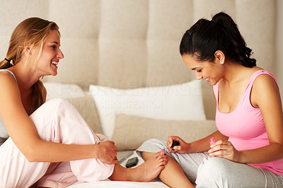 Buy stock photo Portrait of a pretty young woman applying nail polish to a friend's toenails