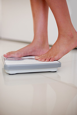 Buy stock photo Lower section legs of a young girl measuring her weight while standing on weighing machine
