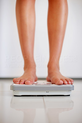 Buy stock photo Lower section legs of a young female measuring her weight while standing on weighing machine