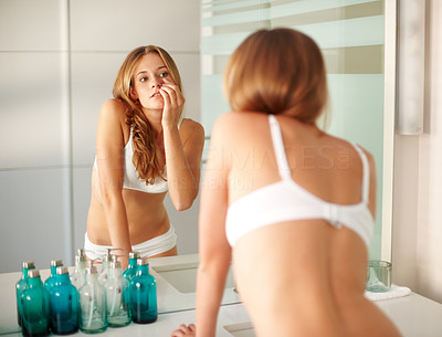 Buy stock photo Portrait of a hot young woman checking her eyes in the bathroom mirror