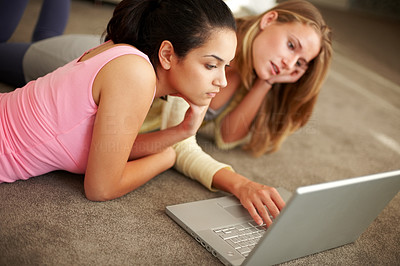 Buy stock photo Portrait of pretty young women using laptop together while lying on the floor