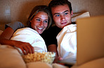 Happy young couple watching interesting movie on laptop
