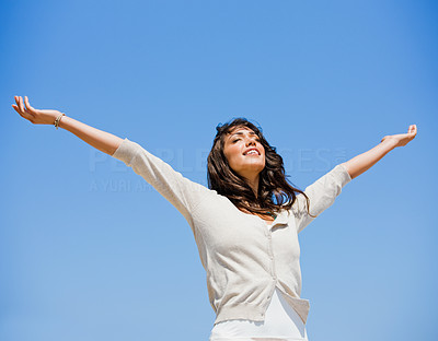 Buy stock photo Pretty young woman with arms raised against blue sky