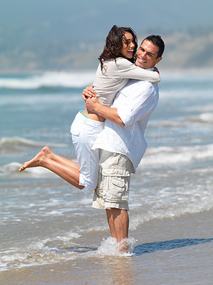 Buy stock photo Beautiful woman laughing while her husband lifts her out of the waves at the seashore