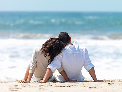 Buy stock photo Rear view of a couple sitting on beach with woman leaning head on man's shoulder