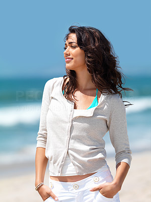Buy stock photo Pretty young woman with hands in pockets standing on beach
