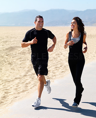 Buy stock photo Smiling young couple jogging on the beach together on a sunny day