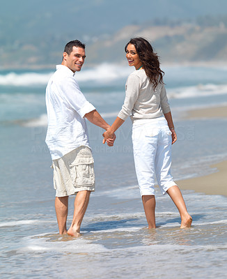 Buy stock photo Young couple in love, at the beach. Enjoying the summer holidays together